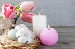 Oeufs et bougies d'arome sur le vieux fond en bois Photographie stock