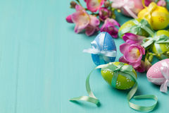 Oeufs et fleurs de pâques colorés sur une table de turquoise Photographie stock