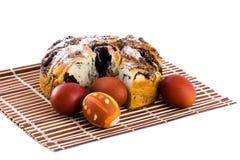 Oeufs et gâteau de pâques sur l'isolat de couvre-tapis Photographie stock libre de droits