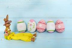 Oeufs et lapin de pâques roses sur un fond en bois bleu Photos libres de droits