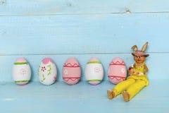 Oeufs et lapin de pâques roses sur un fond en bois bleu Image stock