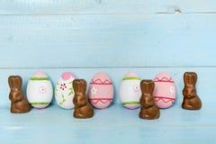 Oeufs et lapins de pâques roses sur un fond en bois bleu Photos libres de droits
