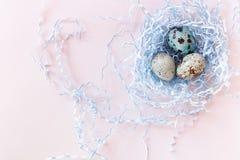 Oeufs et nid de caille de Pâques sur le fond rose Mobilophone jaune Vue supérieure Images stock