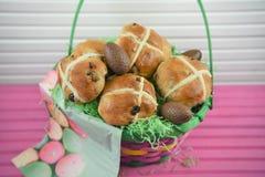 Oeufs et nourriture de pâques de chocolat dans un panier de cadeau avec le fond rose de table Photos stock