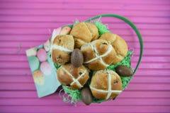 Oeufs et nourriture de pâques de chocolat dans un panier de cadeau avec le fond rose de table Images stock