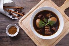 Oeufs et porc cuits dans le plat blanc sur le bloc en bois avec l'ingrédient Photos libres de droits