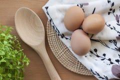 Oeufs faisant cuire pour le petit déjeuner, un jaune de forme de protéine et l'albumen sur un fond blanc, ou sur une table en boi Photos stock