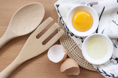 Oeufs faisant cuire pour le petit déjeuner, un jaune de forme de protéine et l'albumen sur un fond blanc, ou sur une table en boi Photographie stock libre de droits