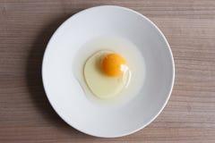 Oeufs faisant cuire pour le petit déjeuner, un jaune de forme de protéine et l'albumen sur un fond blanc, ou sur une table en boi Photo stock
