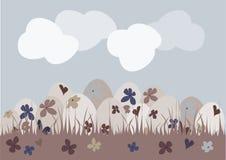 Oeufs floraux dans l'herbe avec le ciel bleu et les nuages Image stock