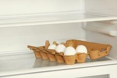 Oeufs frais dans une boîte de papier sur l'étagère de réfrigérateur Images libres de droits