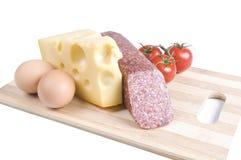 Oeufs, fromage, saucisse et tomates sur un panneau Images libres de droits