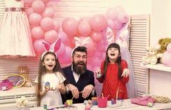 Oeufs heureux de peinture de famille pour P?ques photographie stock libre de droits