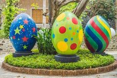 Oeufs multicolores dans l'herbe Chasse à oeufs de pâques, dehors Célébration des vacances de Pâques Photographie stock libre de droits