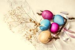 Oeufs peints avec une branche sèche, des fleurs blanches et un ruban de satin Images libres de droits
