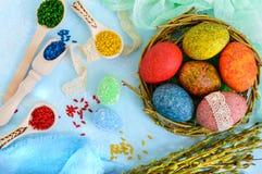 Oeufs peints colorés dans un nid des brindilles du saule sur un fond clair et un riz multicolore pour la peinture décorative Images libres de droits