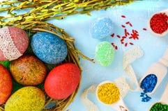Oeufs peints colorés dans un nid des brindilles du saule sur un fond clair et un riz multicolore pour la peinture décorative Image libre de droits