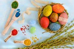 Oeufs peints colorés dans un nid des brindilles du saule sur un fond clair et un riz multicolore pour la peinture décorative Images stock