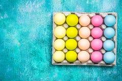 Oeufs peints colorés pour Pâques sur le fond vibrant Configuration plate photos libres de droits