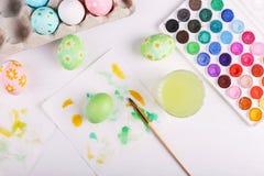 Oeufs, peintures et brosses peints à la main de pâques sur une table blanche Préparation pour les vacances images libres de droits