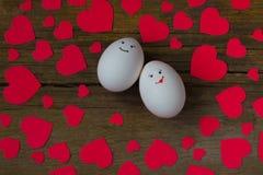 Oeufs peu communs dans l'amour avec le museau et les coeurs rouges Image libre de droits
