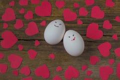 Oeufs peu communs dans l'amour avec le museau et les coeurs rouges Photo stock