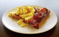 Oeufs sur le pain grillé avec le déjeuner de lard Photographie stock libre de droits
