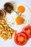 Oeufs sur le plat avec des champignons de couche, des haricots et la tomate Images stock