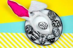 oeufs teints dans un plat avec des oreilles de lapin sur un fond jaune et bleu vibrant images stock