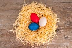 Oeufs tricolores de Pâques sur un fond en bois dans le nid situé sur le milieu Image stock