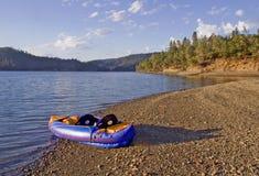 Oever van het meer met opblaasbare kajak Stock Afbeeldingen