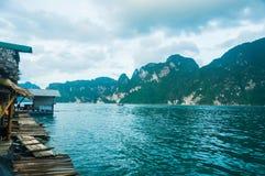 Oever van het meerplattelandshuisjes en bergen Stock Foto's