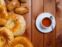 Oezbekistaans brood met kop thee op donkere achtergrond stock afbeelding
