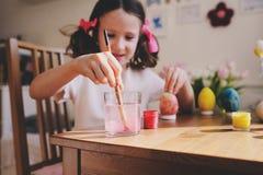 Ofício da Páscoa com crianças - a pintura eggs em casa Decorações sazonais da mola imagens de stock royalty free