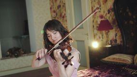Ofício musical de apenas, violinista profissional, sentando-se na cama e no jogo vídeos de arquivo