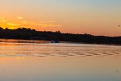 Ofício ou barco de água no lago no crepúsculo com ondinhas no lago imagens de stock royalty free