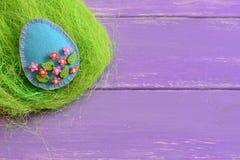 Ofícios do ovo da páscoa com os grânulos plásticos coloridos Ornamento do ovo de feltro no ninho e no fundo de madeira com espaço imagem de stock