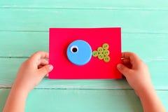 Ofícios dos peixes Criança que guarda um cartão com peixes do ofício Tampões de garrafa de DIY Ideias criativas do tampão de garr Imagem de Stock Royalty Free