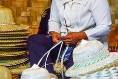 Ofícios tailandeses - teça um chapéu pelas mulheres tailandesas, ingredientes naturais no festival tailandês do turismo na noite foto de stock