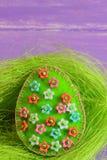 Ofícios verdes do ovo da páscoa com os grânulos plásticos coloridos Ofícios do ovo de feltro no ninho e no fundo de madeira Cartã fotos de stock