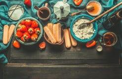 Oförfalskade italienska ingredienser för jordgubbetiramisumatlagning på det mörka lantliga köksbordet Royaltyfria Foton