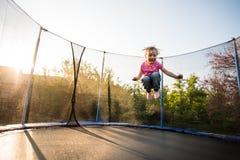 Oförskräckt liten unge som högt hoppar på trampolinen Arkivbilder