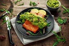 Ofen kochte Lachssteak, Leiste mit Avocadosalsa und Grün auf Schwarzblech Hölzerne Tabelle Gesunde Nahrung stockfotografie