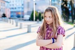 Ofendido dez anos de azul velho eyed a menina na cidade Fotografia de Stock