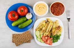 Ofenkartoffeln in der Platte, in den Gurken, in den Tomaten und in der Soße in den Schüsseln Stockbilder