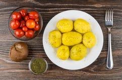 Ofenkartoffeln in der Platte, in den Schüsseln mit marinierten Tomaten und im Dill Lizenzfreies Stockfoto