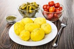 Ofenkartoffeln in der Platte, Schüsseln mit marinierten Essiggurken, Tomaten Stockbild