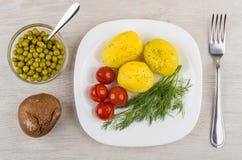Ofenkartoffeln mit Dill, in Essig eingelegte Tomaten in der Platte, grüne Erbsen Lizenzfreies Stockfoto