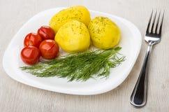 Ofenkartoffeln mit Dill, in Essig eingelegten Tomaten in der Platte und Gabel Lizenzfreie Stockbilder