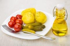 Ofenkartoffeln mit in Essig eingelegten Tomaten, Essiggurken, Gabel in der Platte Stockfoto